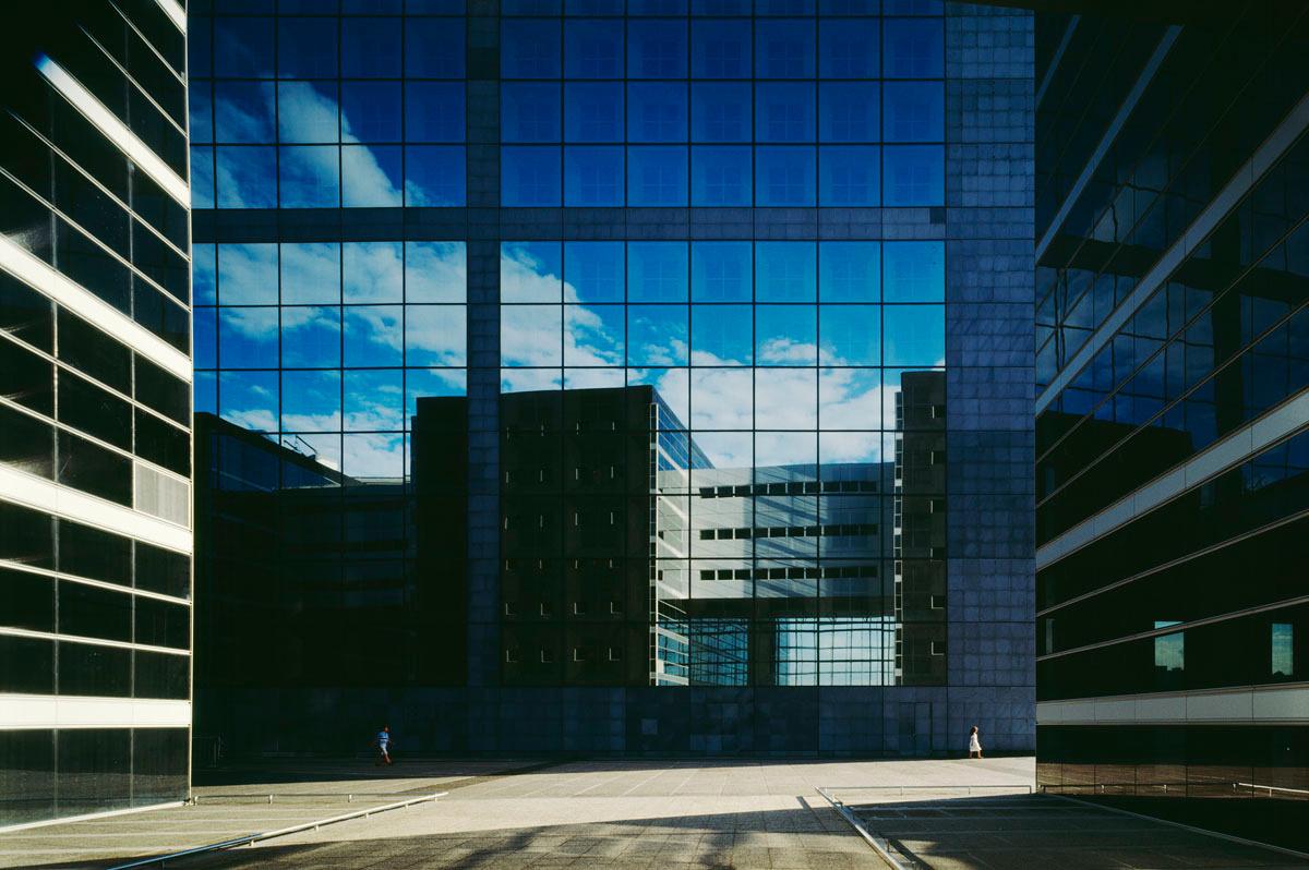 La photographie montre le reflet d'un édifice sur une façade de verre.