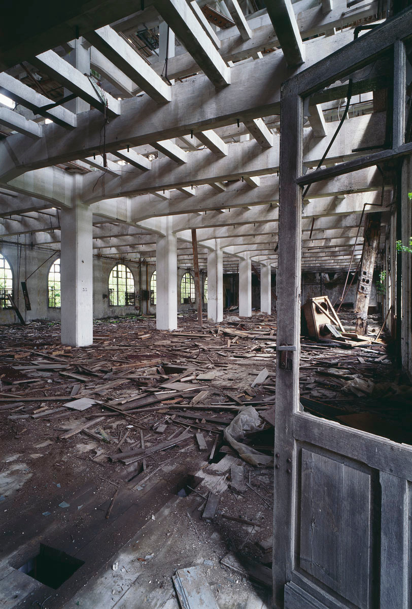 La photographie montre l'intérieur ruiné d'un bâtiment à structure de béton.
