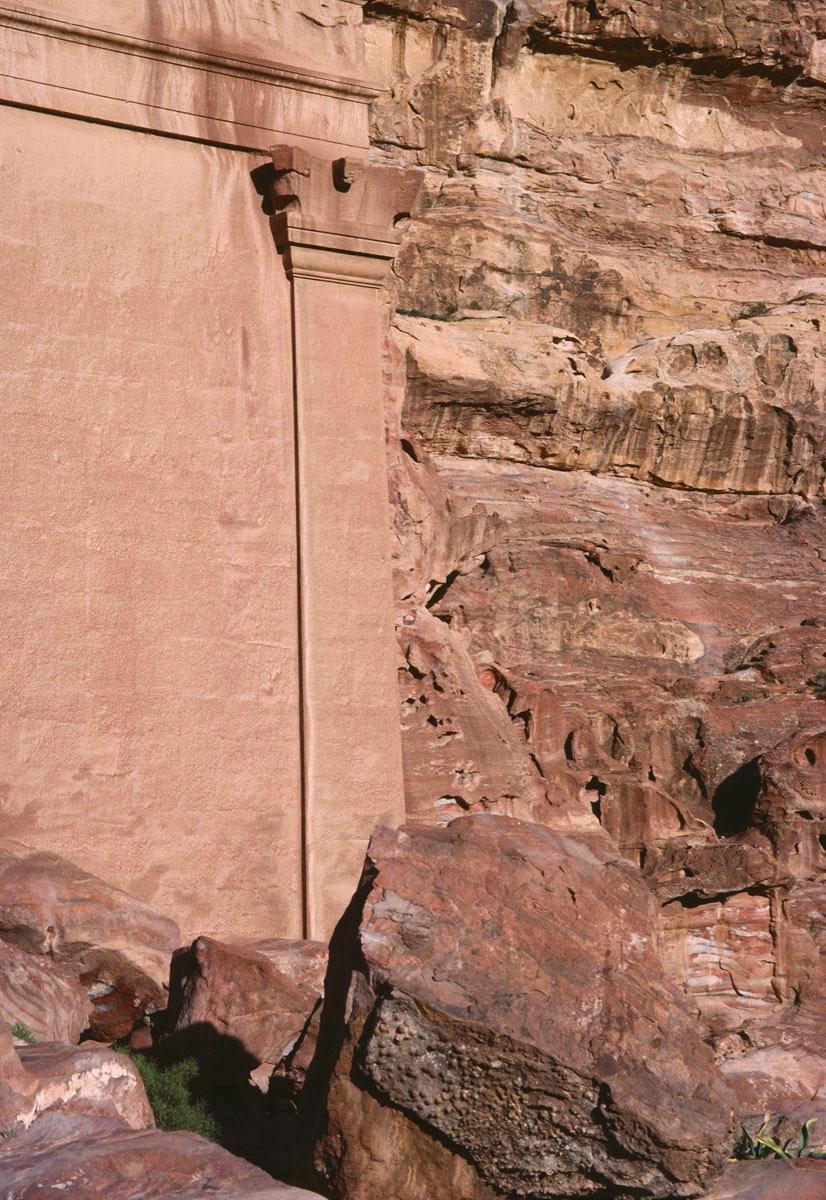 La photographie montre un pilastre taillé dans le rocher.