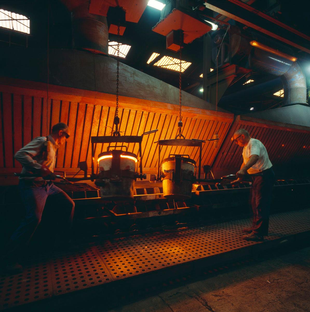 La photographie montre des mouleurs au travail dans l'usine Godin SA