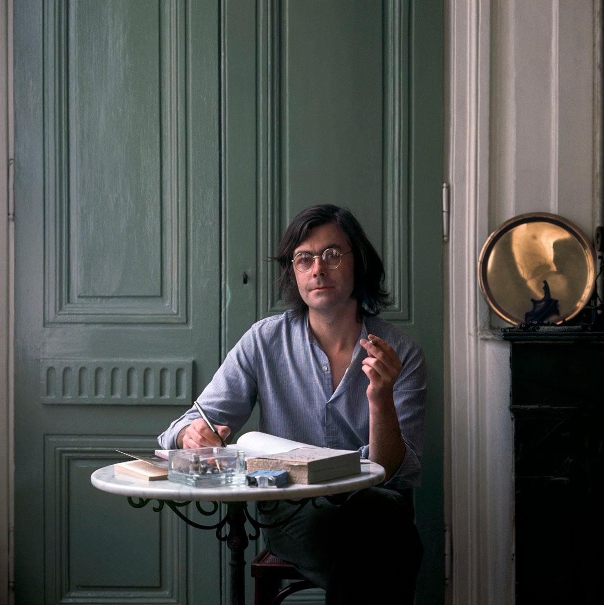 La photographie montre un homme assis à un guéridon, un stylo à la main.