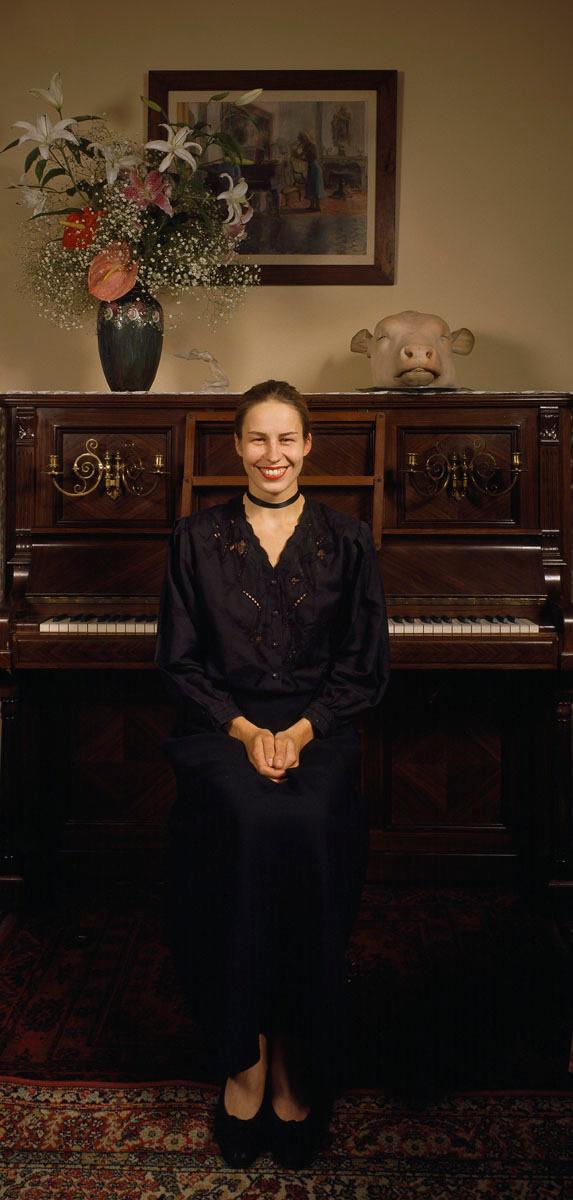 La photographie montre une jeune femme souriante assise dos à un piano