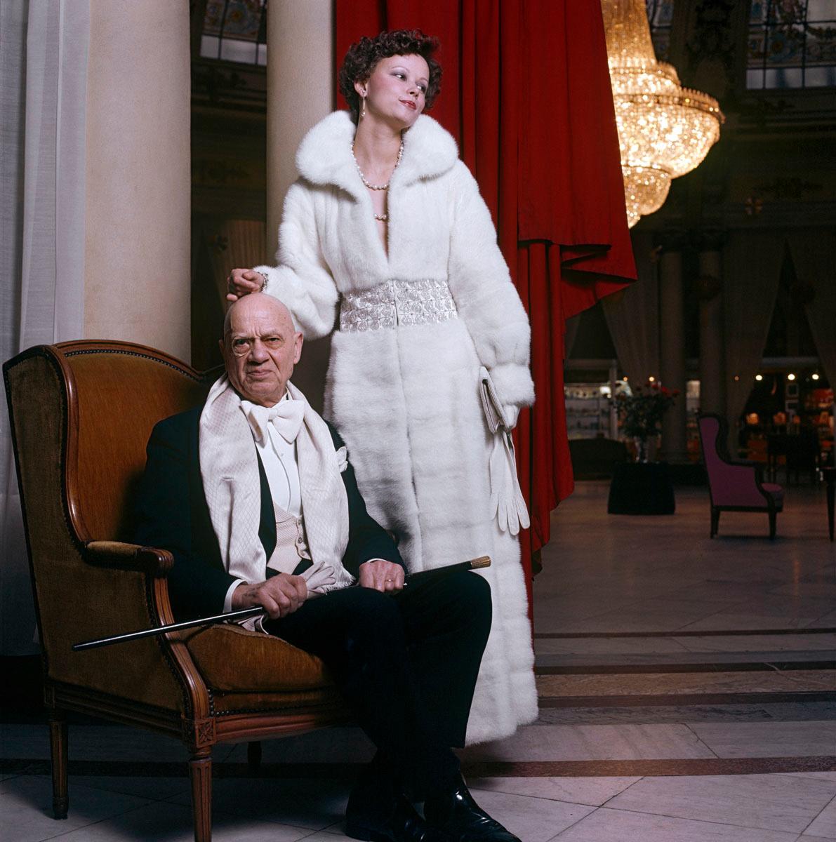 La photographie montre une femme en fourrure et un homme âgé.