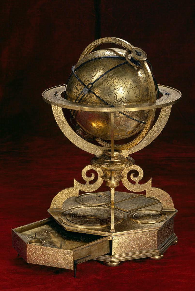 La photographie montre un globe céleste en métal cuivré.