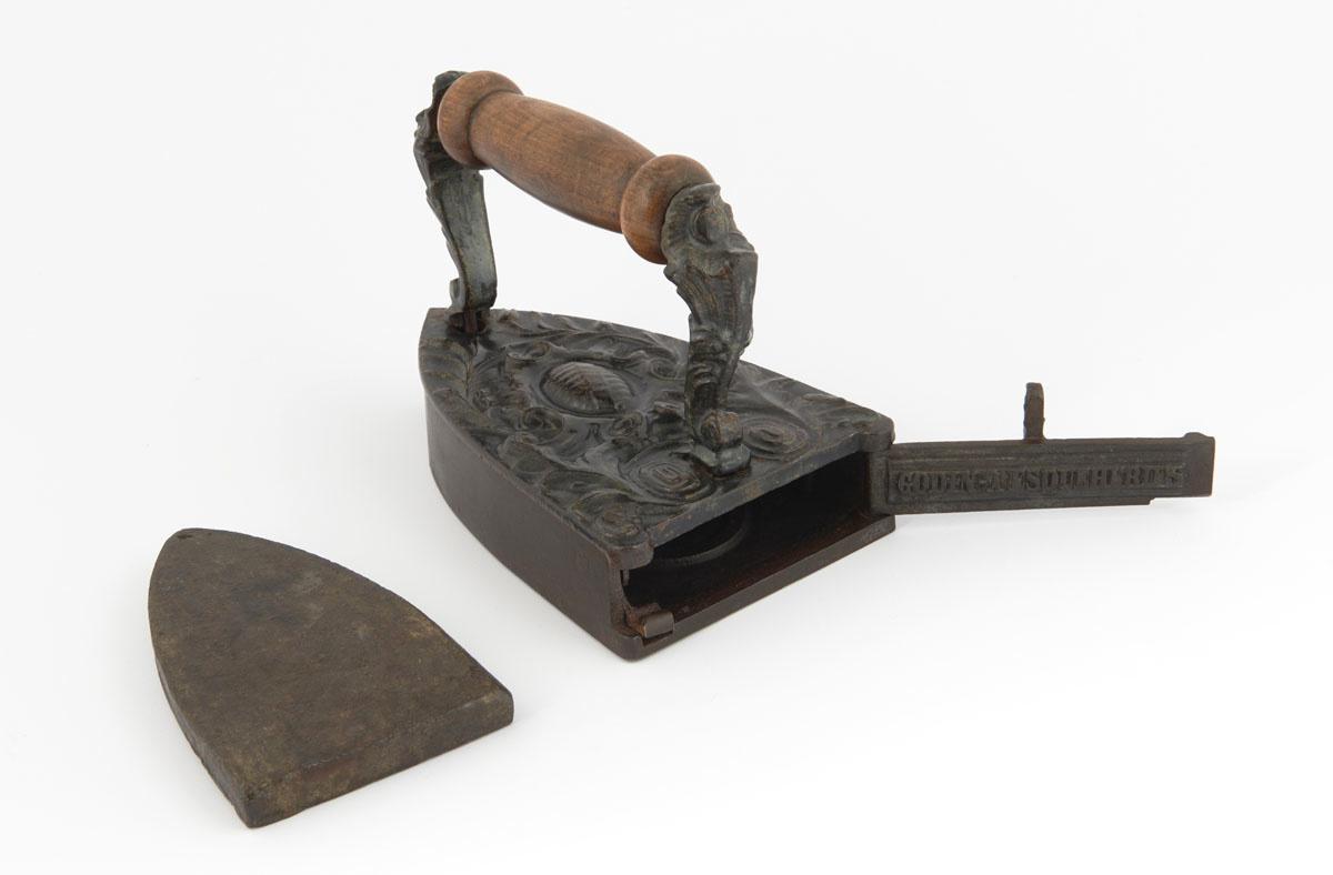 La photographie montre le fer à repasser et son lingot.