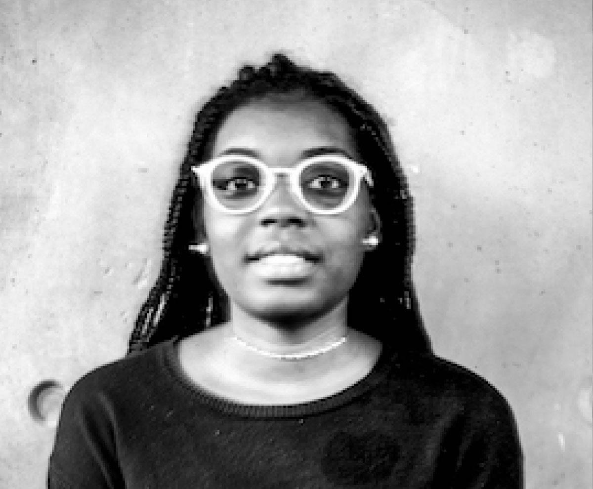 Portrait en buste d'une jeune femme noire à lunettes