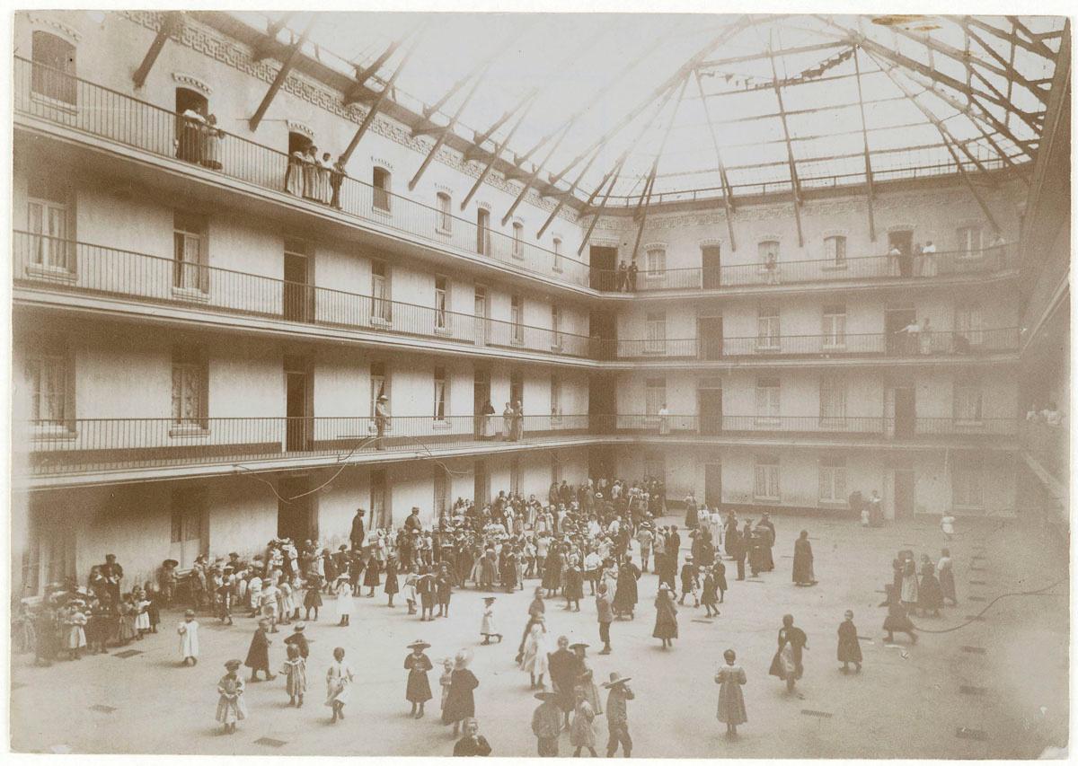 Vue d'écoliers rassemblés dans la cour du pavillon central.