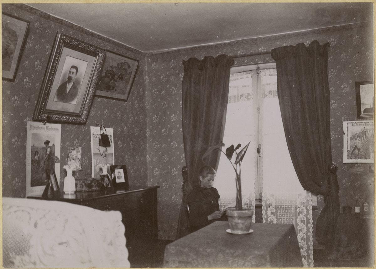 Vue d'une chambre à coucher avec une jeune fille lisant près de la fenêtre