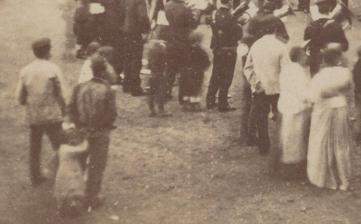 Vue en plongée d'un attroupement autour de musiciens sur la place du Familistère