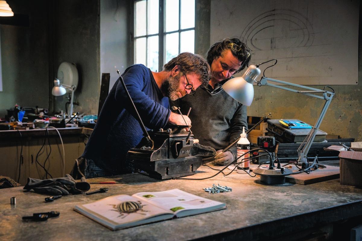 Photographie de deux hommes dans un atelier.