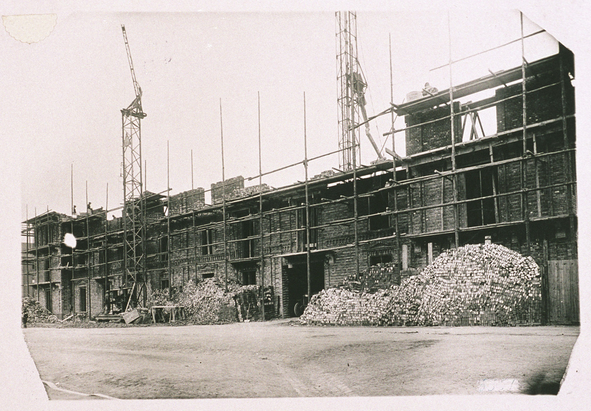Devant la façade sud en reconstruction de l'aile gauche du Palais social du Fami