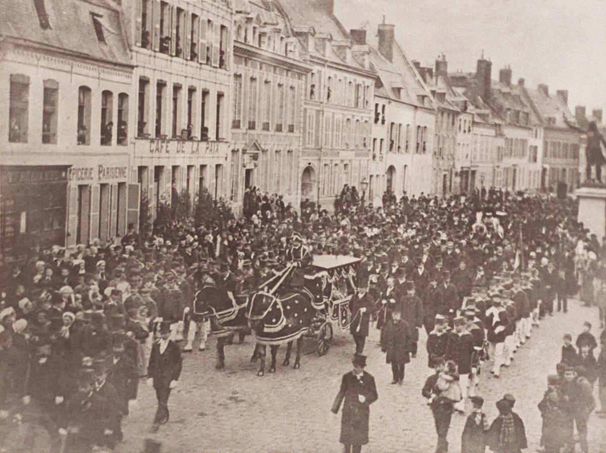 Le convoi funéraire de Godin, suivi par une foule nombreuse, s'avance sur la pla