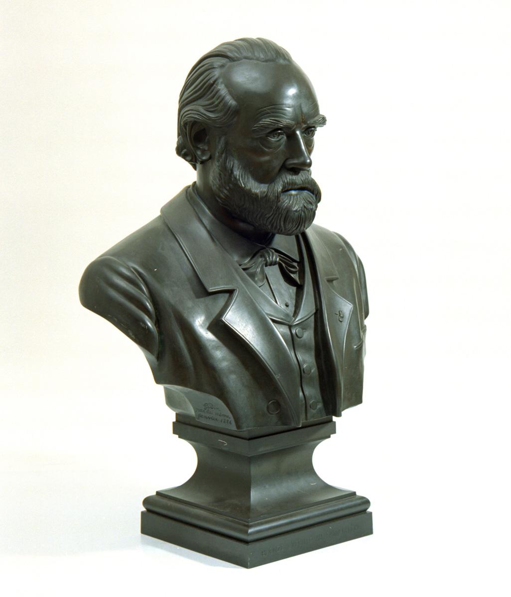 La sculpture en bronze représente Godin en buste.