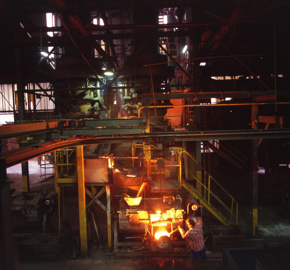 La photographie montre une coulée de fonte irradiant l'atelier de fonderie de l'
