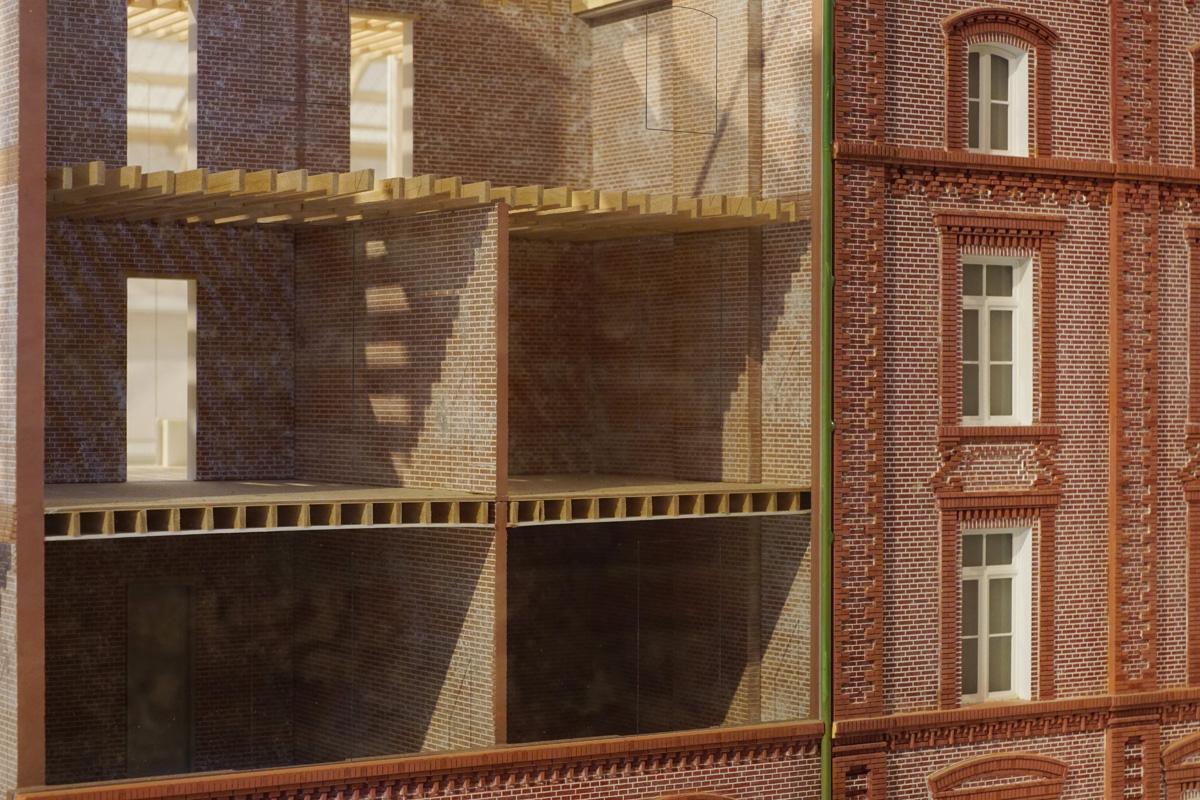 La photographie montre un écorché de la maquette sur le système constructif.