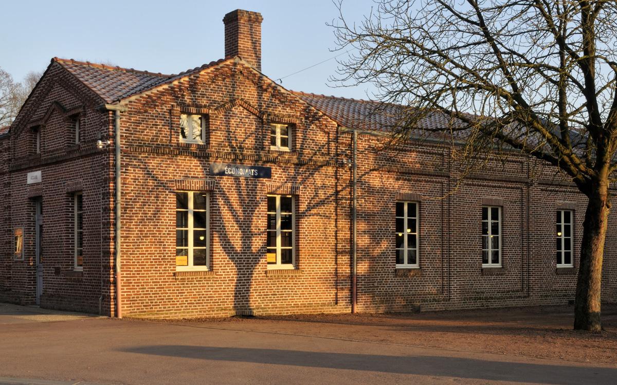 L'ombre d'un arbre se projette sur la façade des économats.