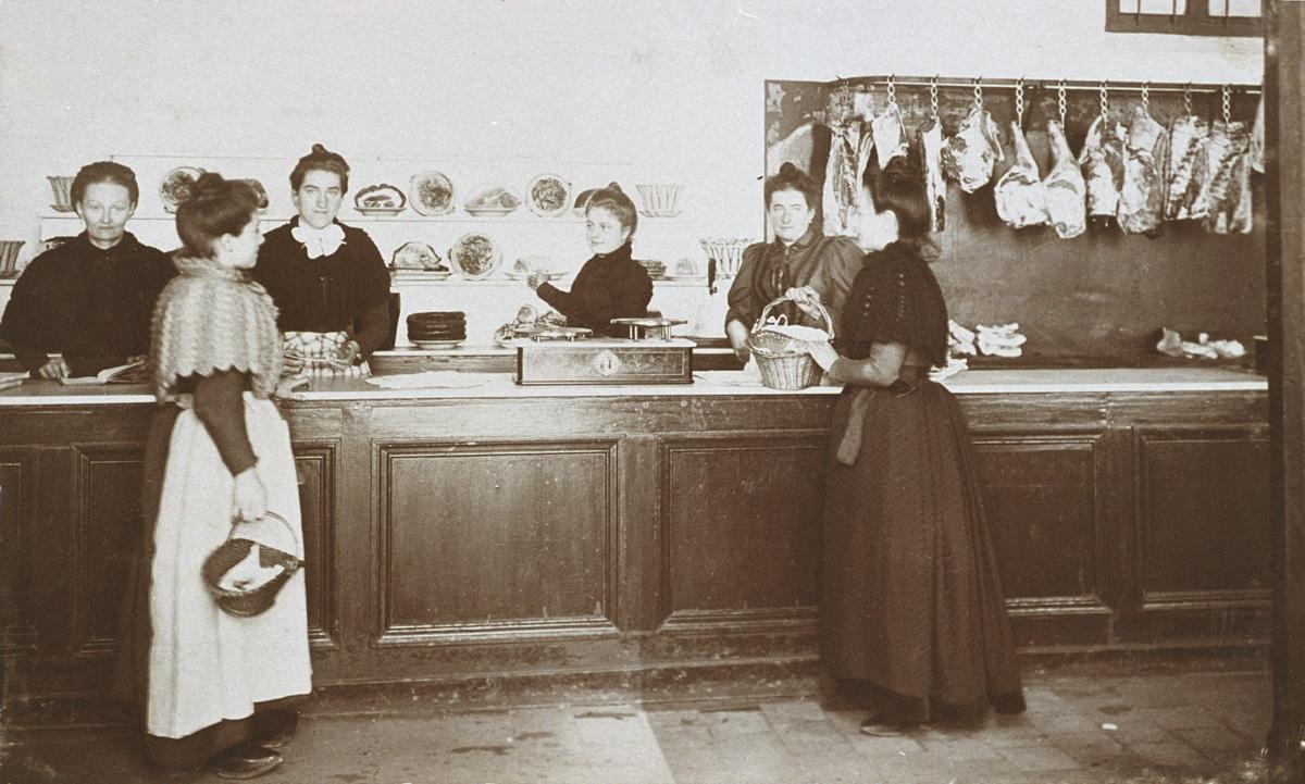 La photographie met en scène acheteuses et vendeuses de la boucherie.