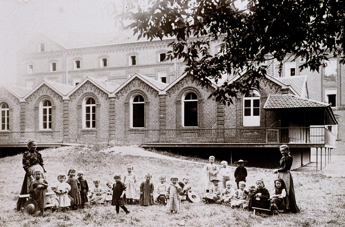 Des enfants posent sur l'herbe, devant la crèche du Familistère.