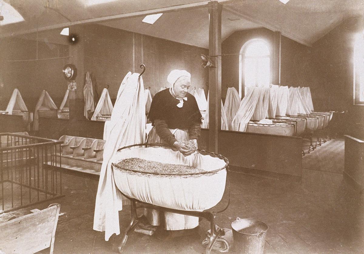 Madame Roger prépare le matelas d'un berceau de la nourricerie du Familistère.