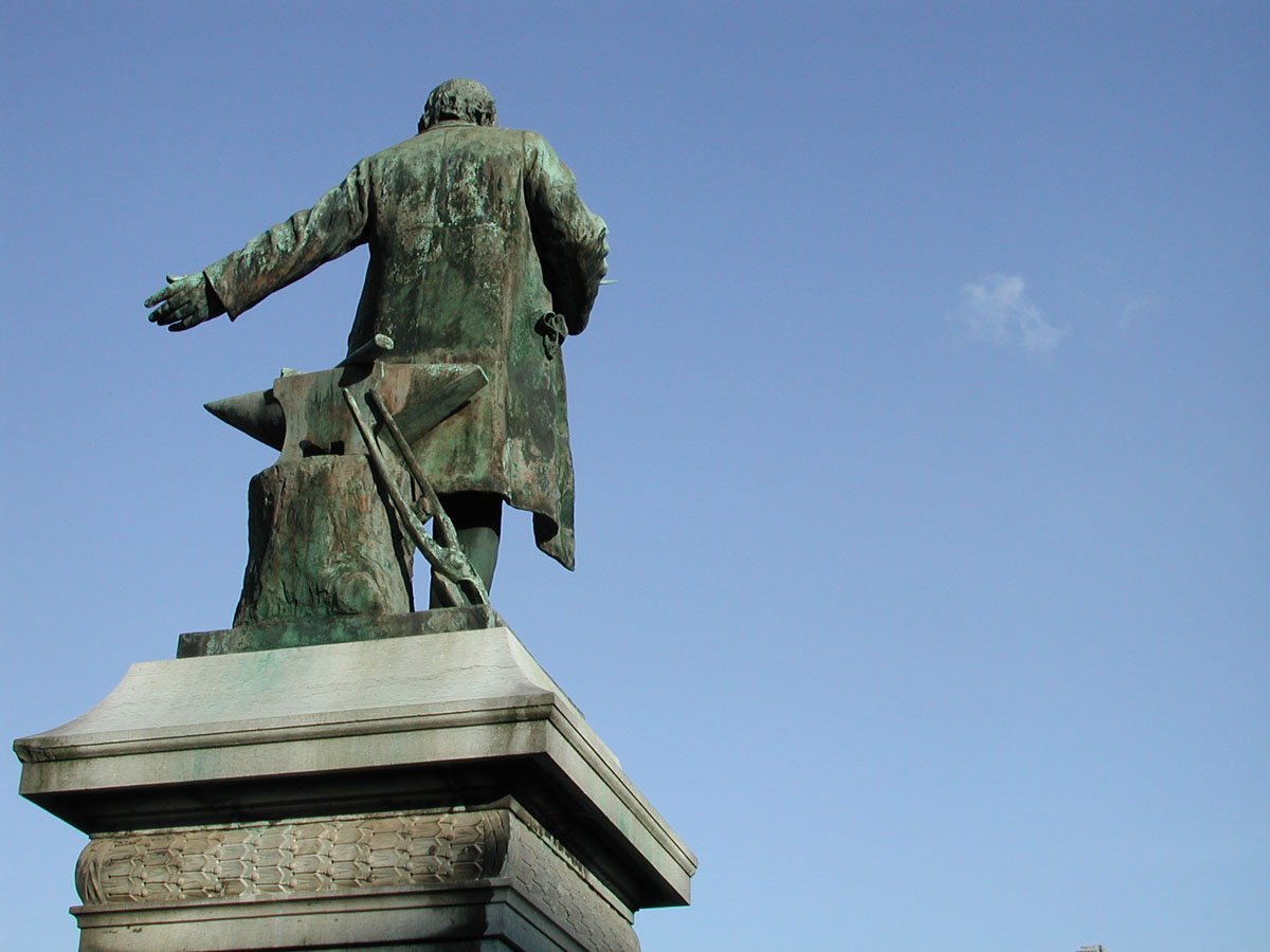 La statue de Godin se détache sur un ciel bleu uniquement taché par un petit nua