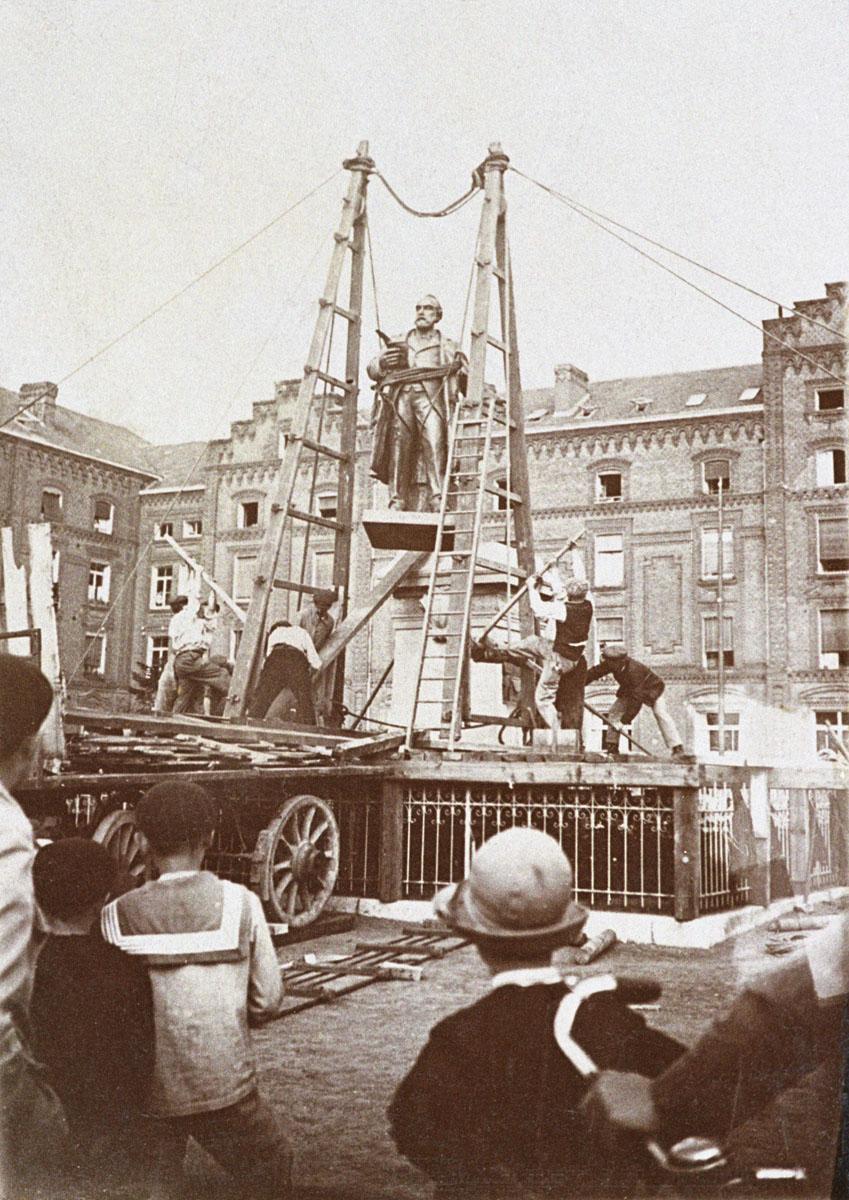 La seconde statue de Godin est en cours d'installation sur le piédestal.