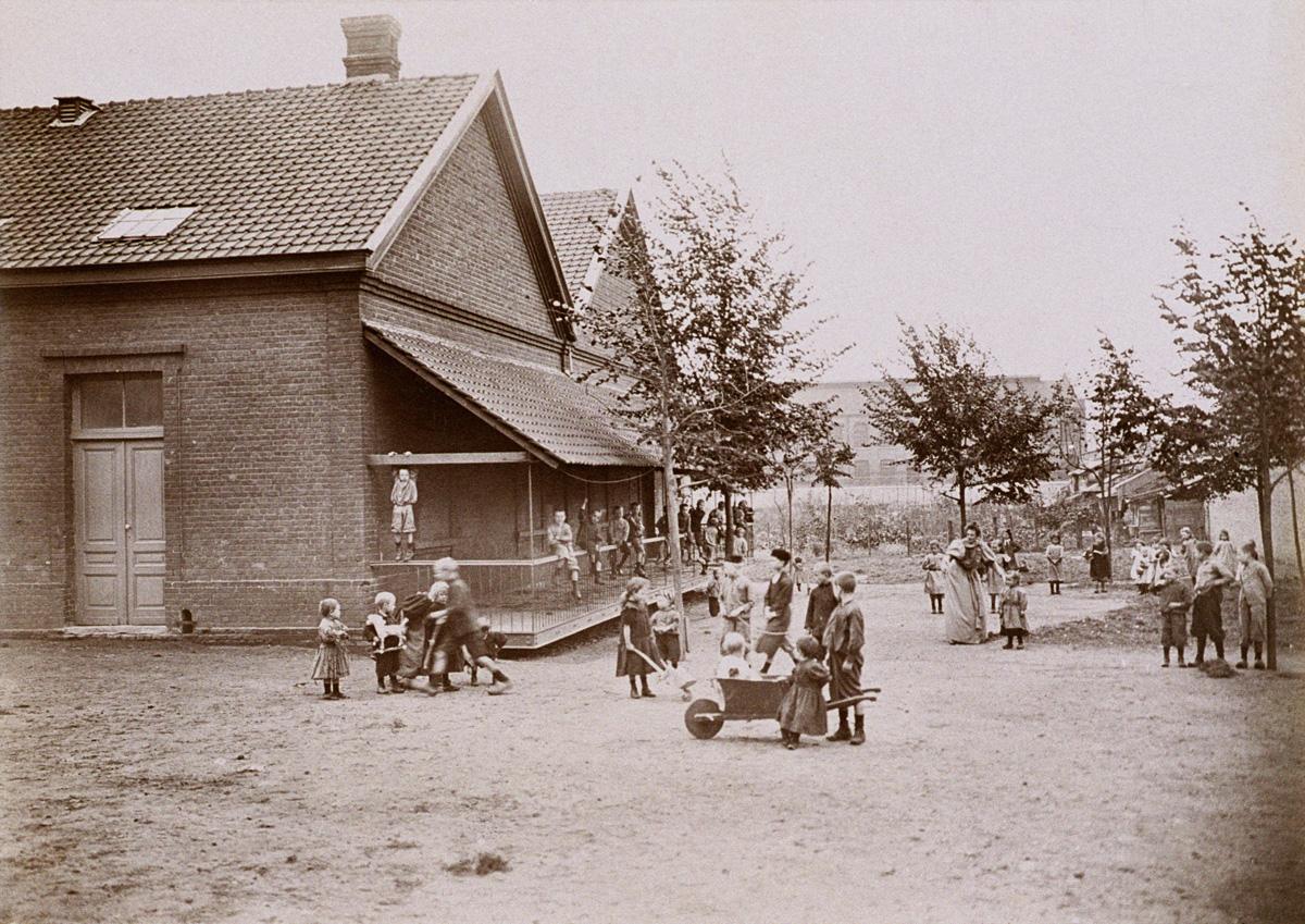 Des enfants jouent devant l'école du Familistère de Laeken.