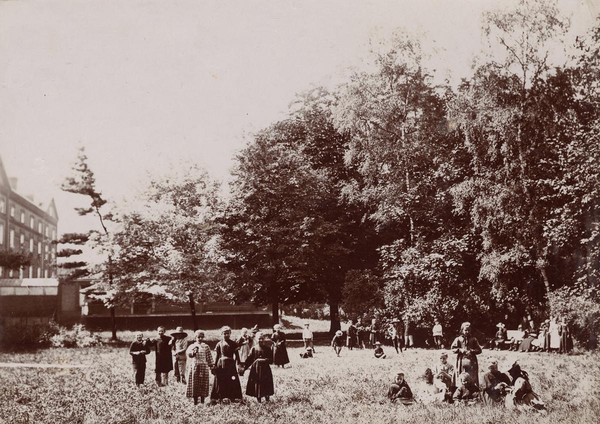 Des enfants sont sur la pelouse au nord du Palais social à côté de la nourriceri