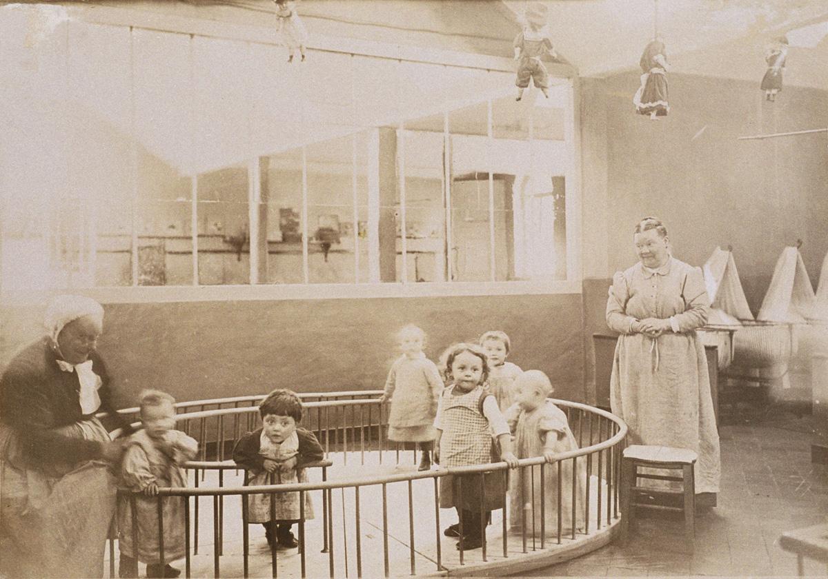 Des enfants posent sur le promenoir de la nourricerie du Familistère