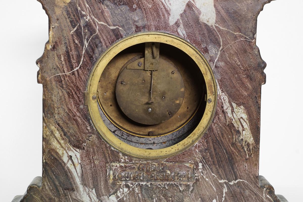La pendule n° 5 en fonte de fer émaillée en vert est vue de dos.