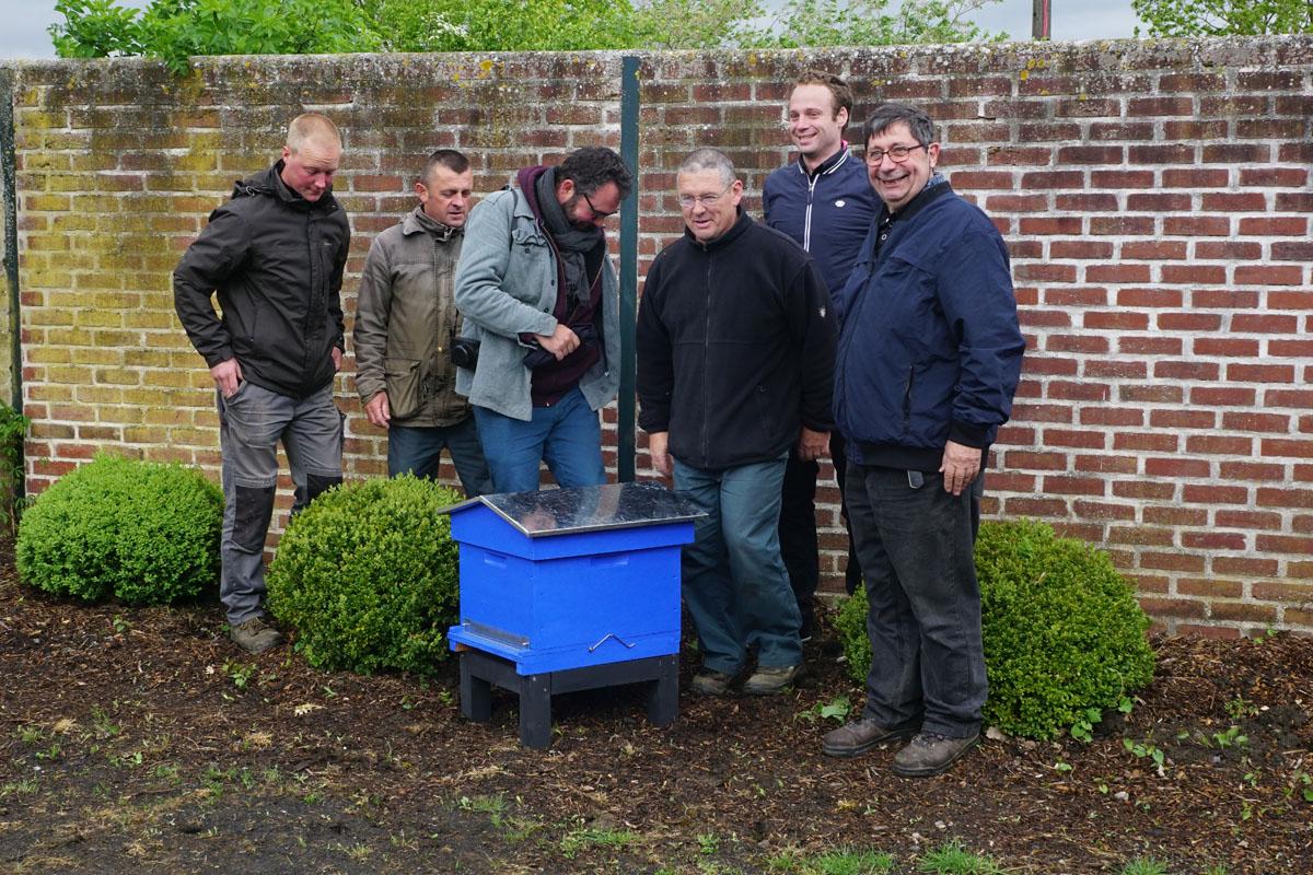 Un groupe est photographié derrière la ruche du jardin d'agrément