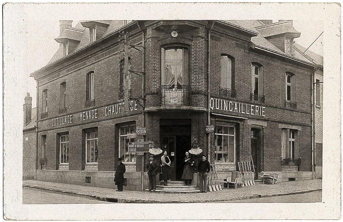 La carte postale montre la façade d'un magasin de quincaillerie.