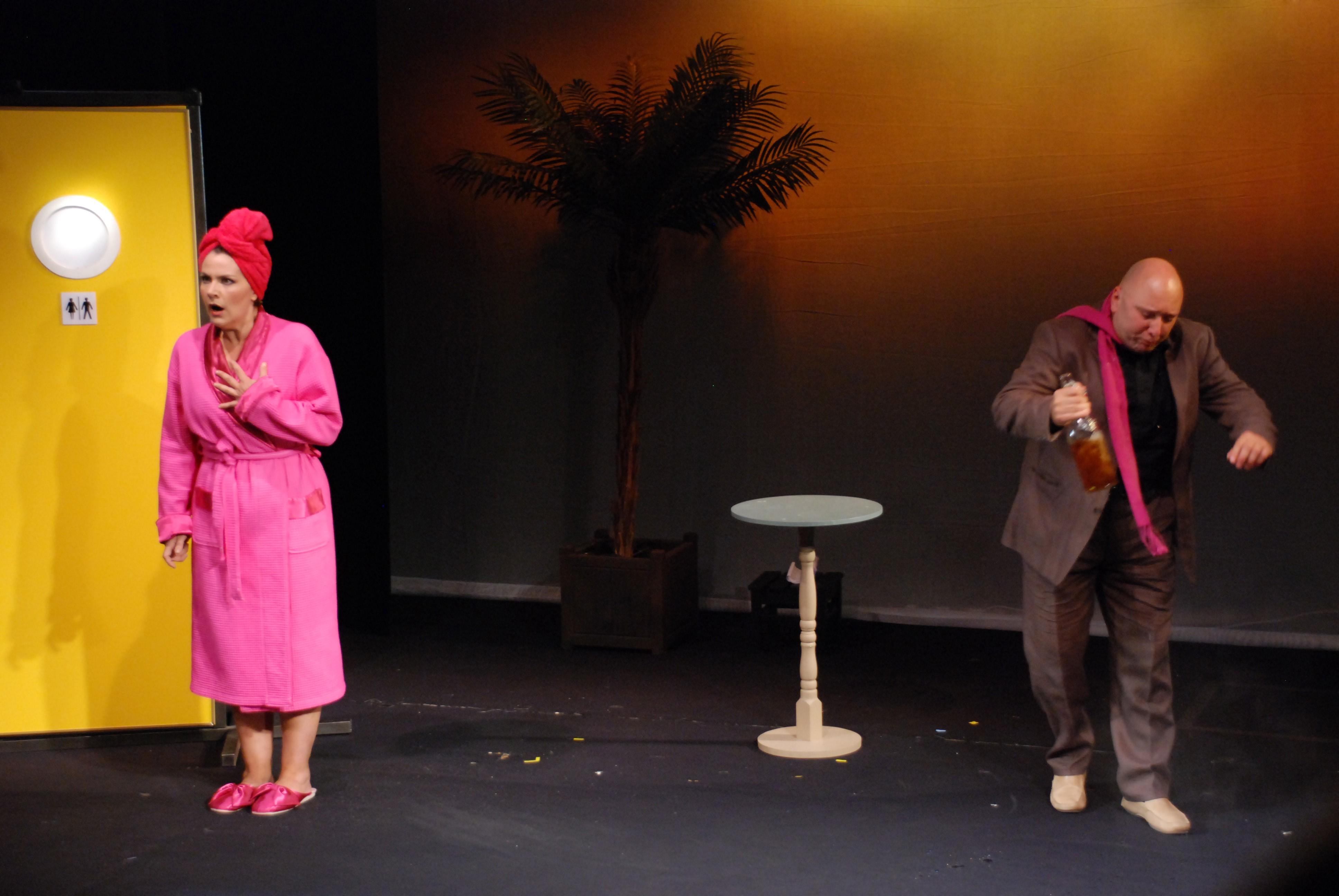 Deux personnes sur scène dans un décor minimaliste.