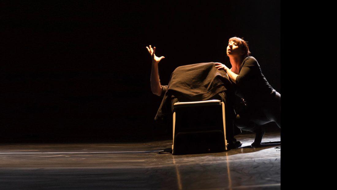 Sur une scène sombre une femme semble danser près d'une chaise où un homme se ca