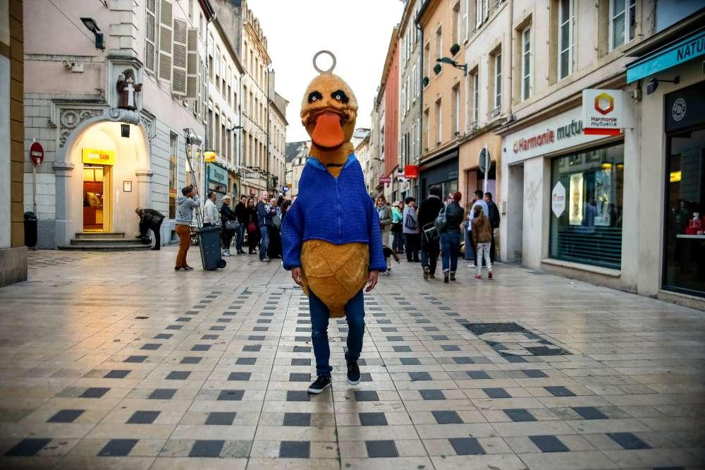 Un homme en costume de canard au milieu d'une rue pietonne cmmecrçante.
