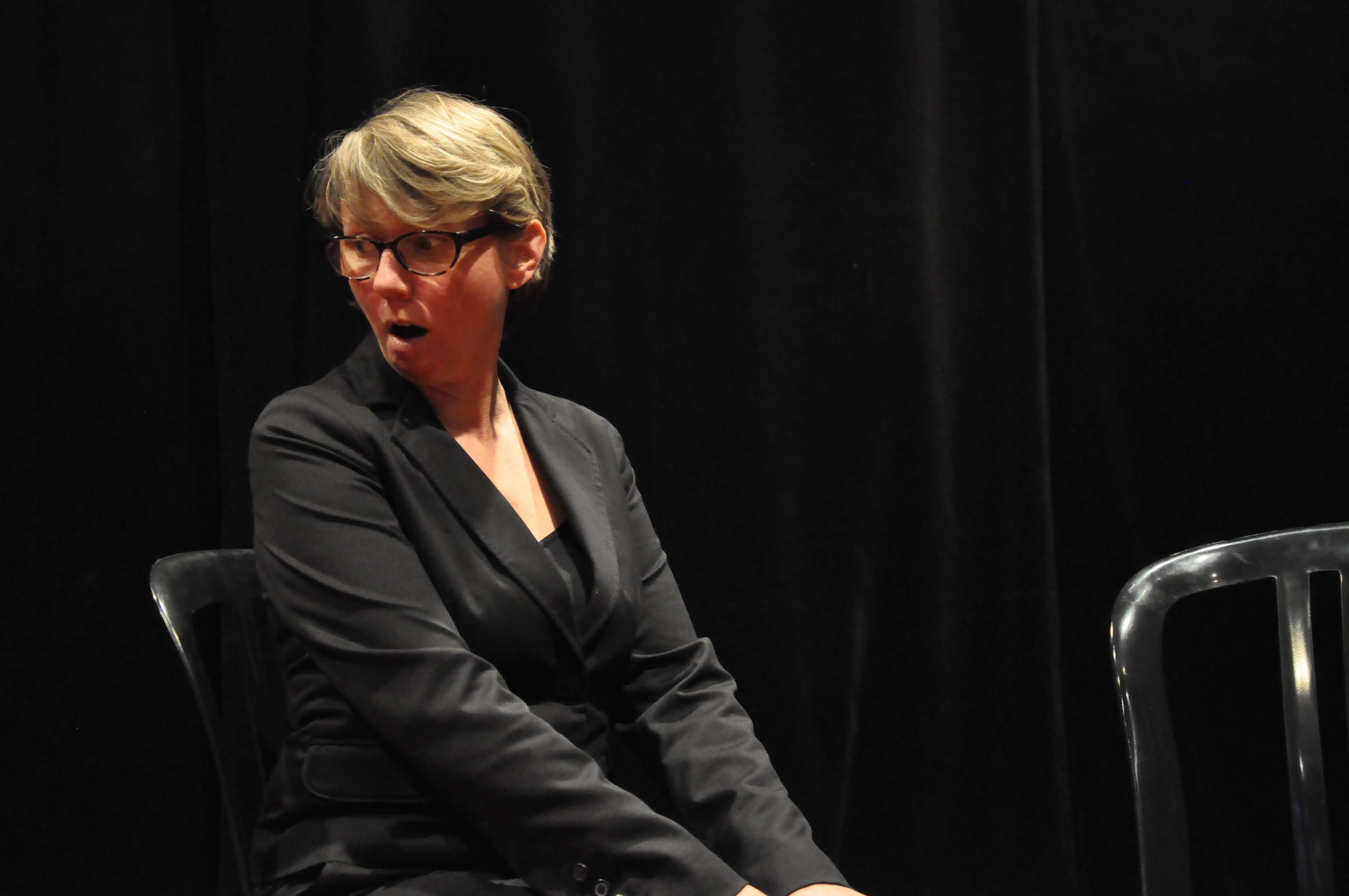 Une femme en tailleur noir, assise, se tournant de côté en faisant la grimace.