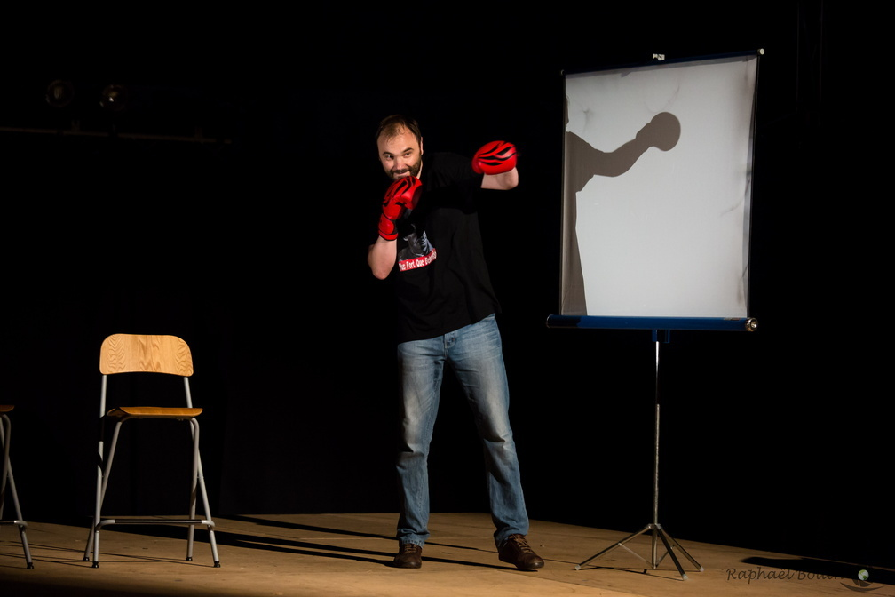 Un homme avec des gants de boxe au milieu d'une scène entre un tabouret et un pa