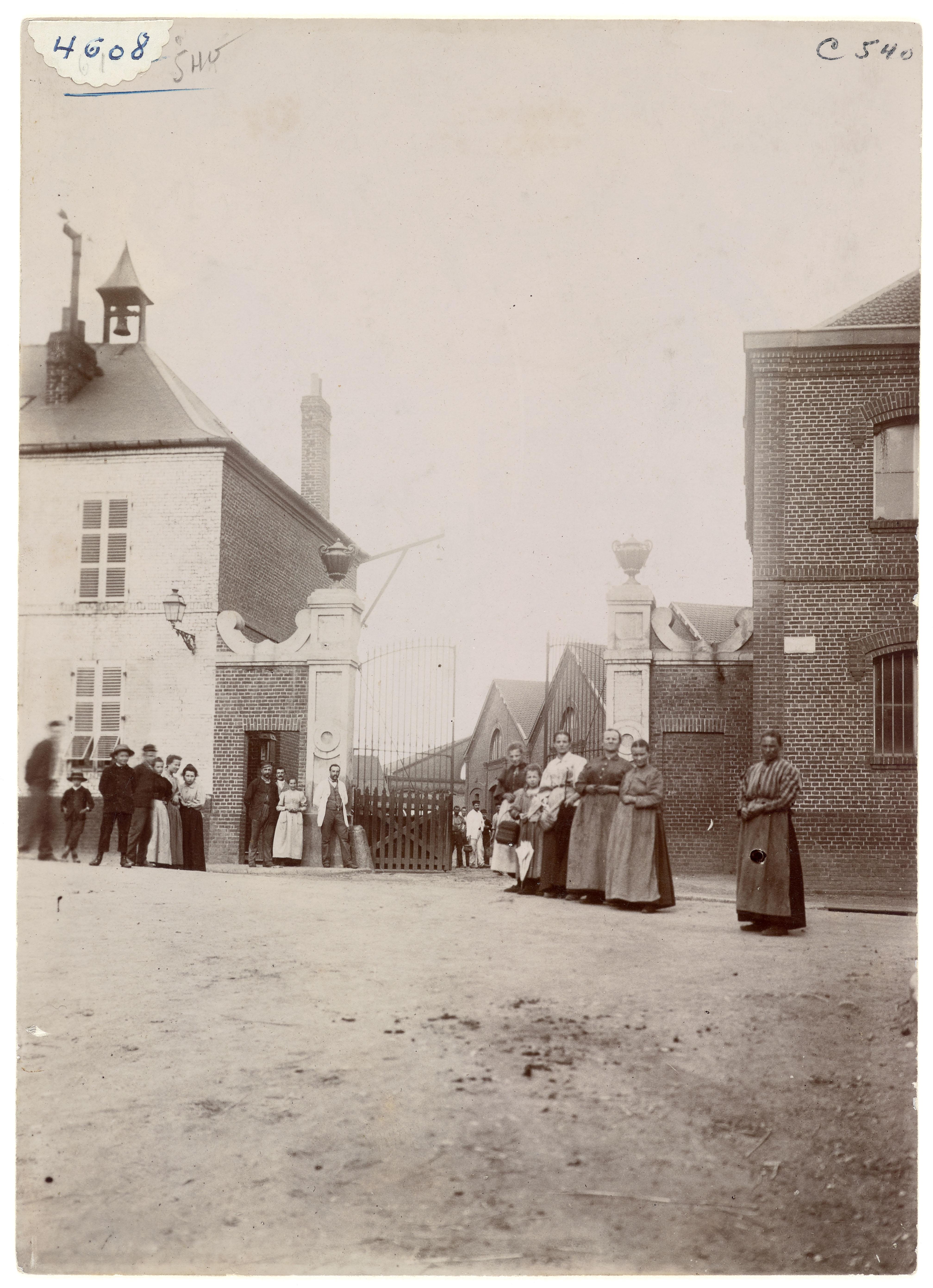 La photographie montre des personnes devant le portail d'entrée de l'usine du Fa