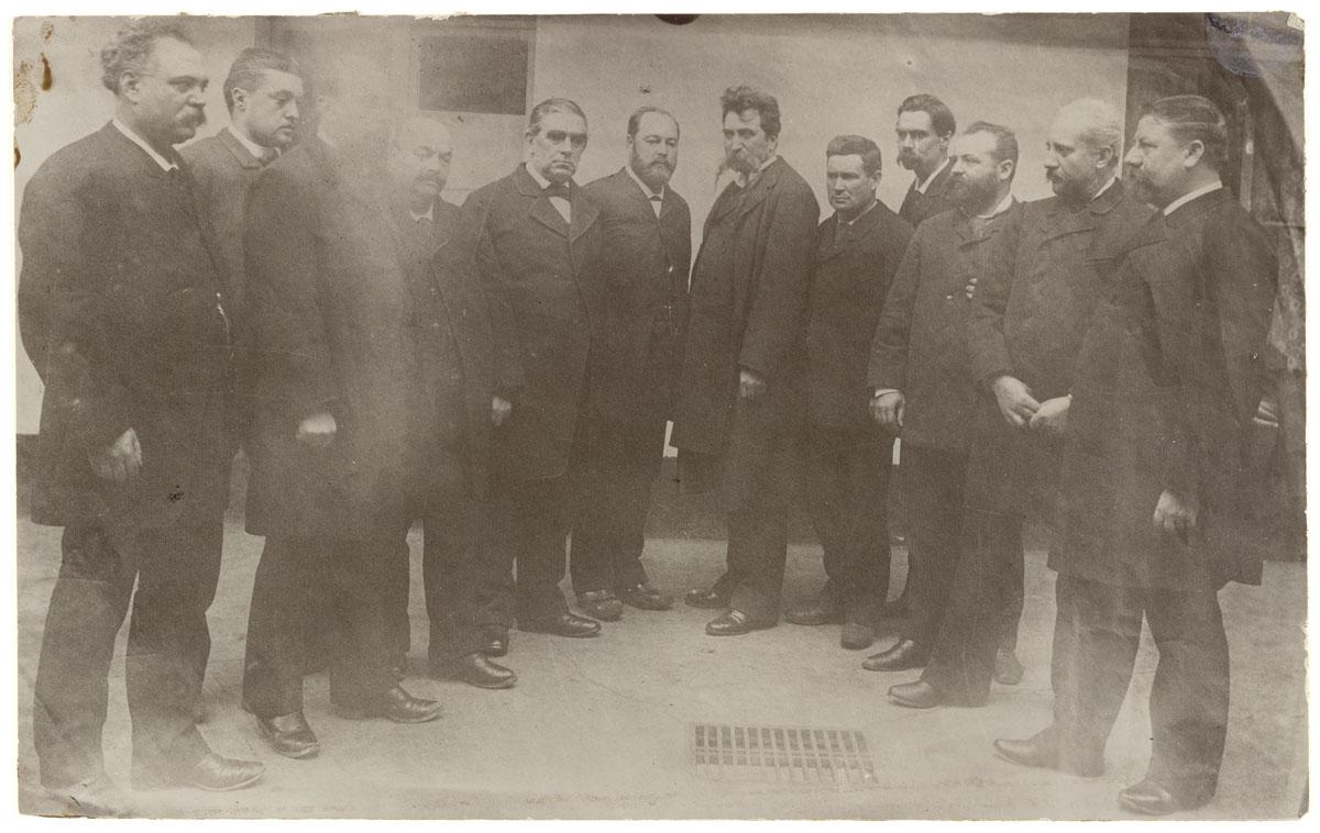 La photographie est un portrait collectif d'hommes dans une cour du Familistère