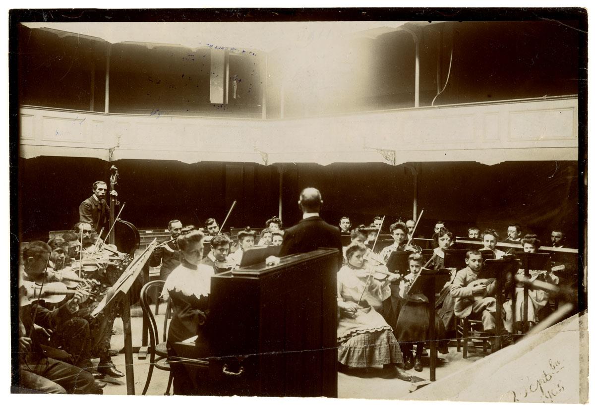 La photographie montre une répétition d'orchestre à l'intérieur du théâtre du Fa