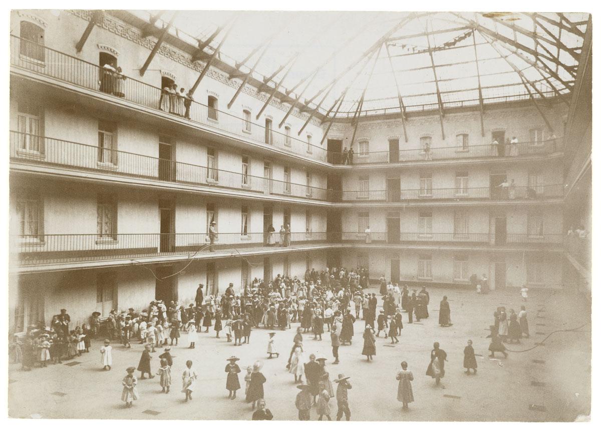 La photographie montre la cour du pavillon central envahie par des enfants.