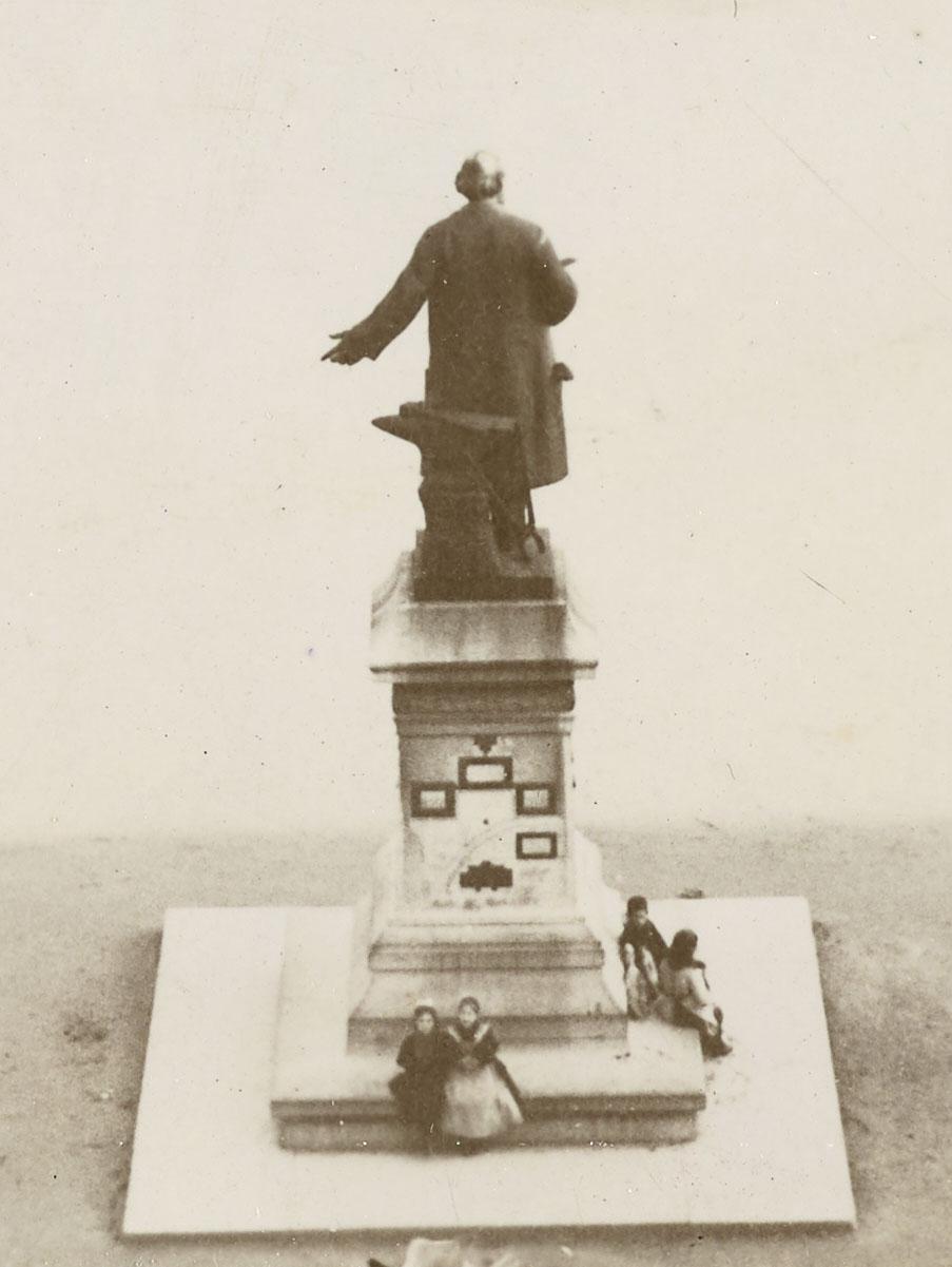 Le détail de la photographie montre le monument à Godin sur la place du Familist