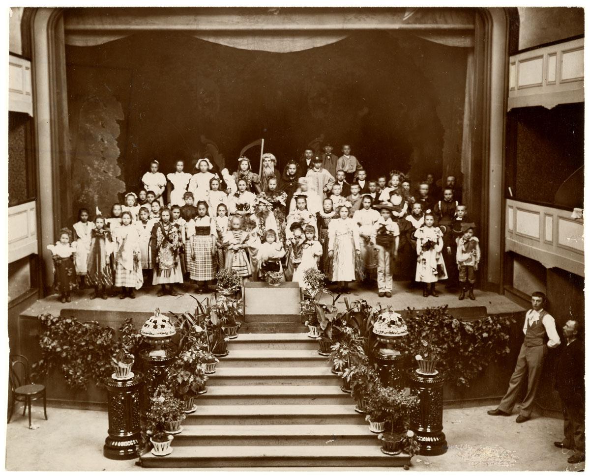 La photographie montre des enfants costumés sur la scène du théâtre du Familistè