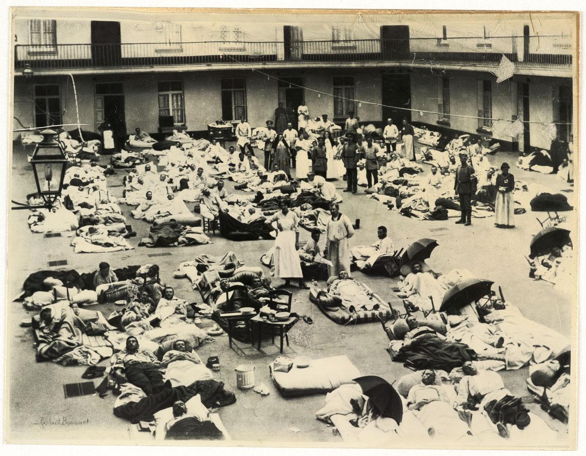 La photographie montre des soldats blessés couchés dans al cour du pavillon cent