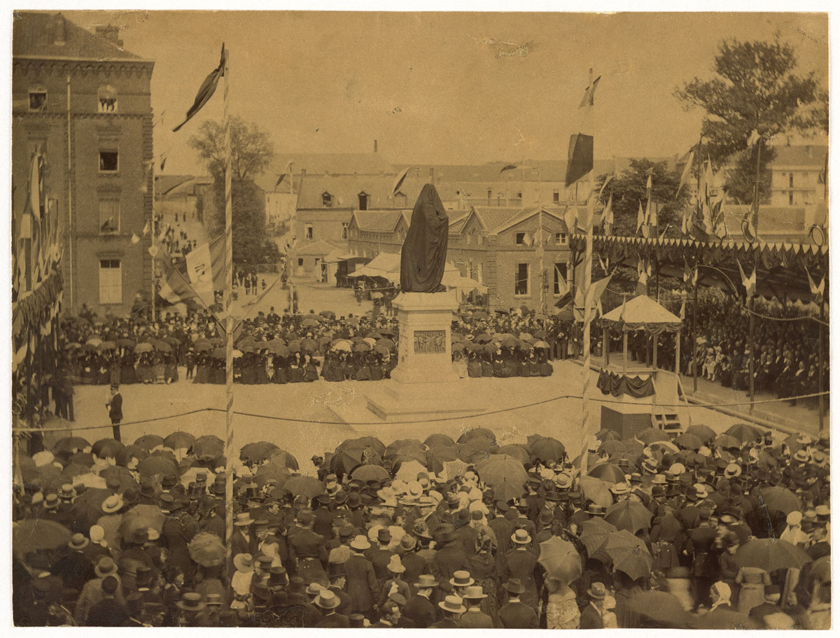 La photographie montre l'inauguration de la statue de Godin, encore voilée
