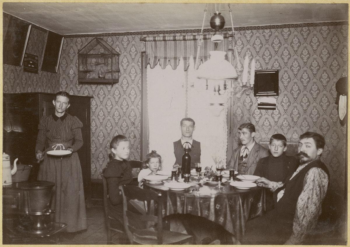 La photographie montre une famille attablée dans la cuisine d'un logement du Fam