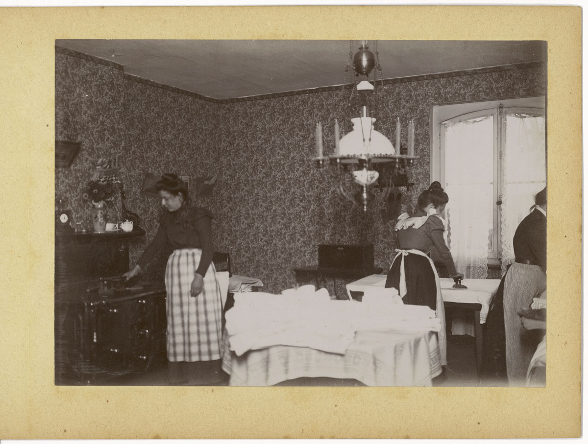 La photographie montre une scène de repassage dans la cuisine d'un logement du F