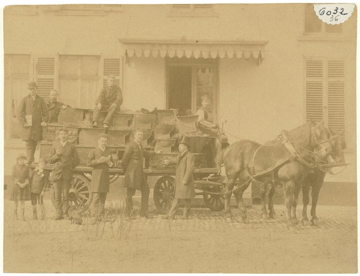 La photographie montre une voiture à cheval chargée de cuisinières.