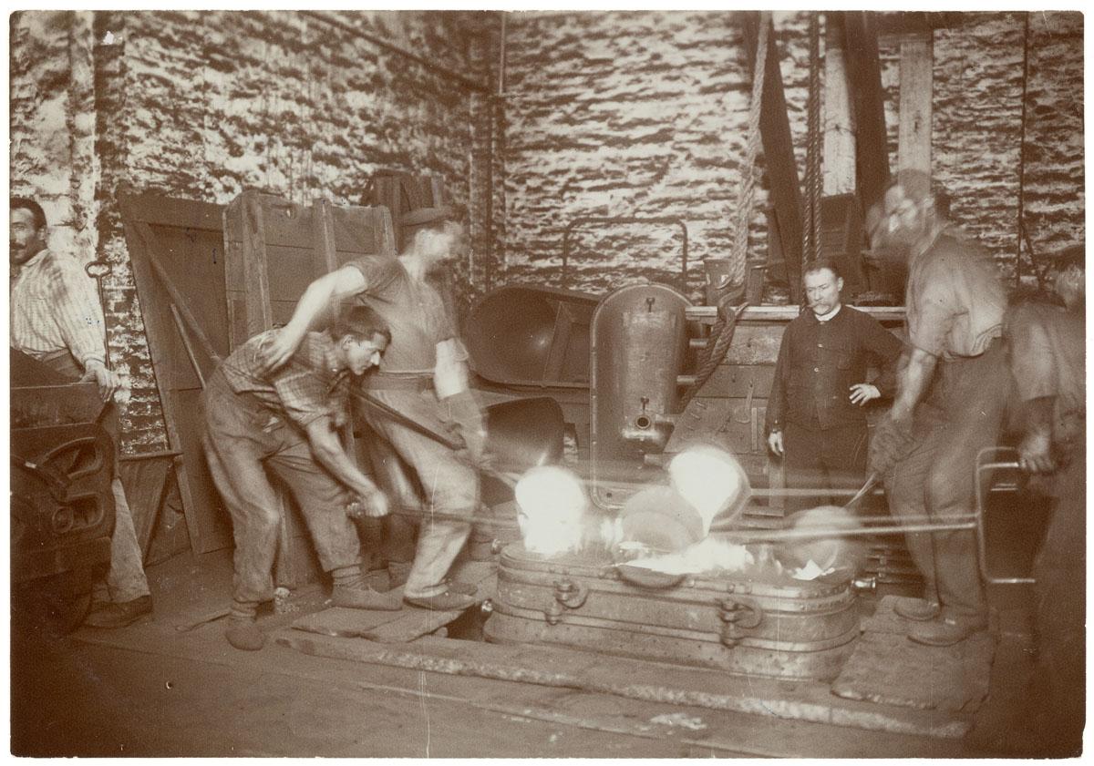 La photographie montre une scène de moulage dans l'usine du Familistère