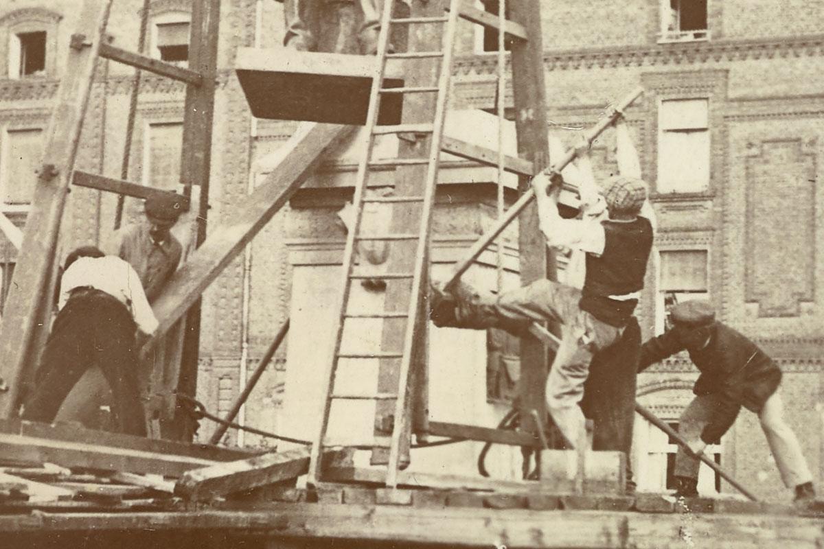 Détail de la photographie de l'installation de la statue de Godin sur son piédes