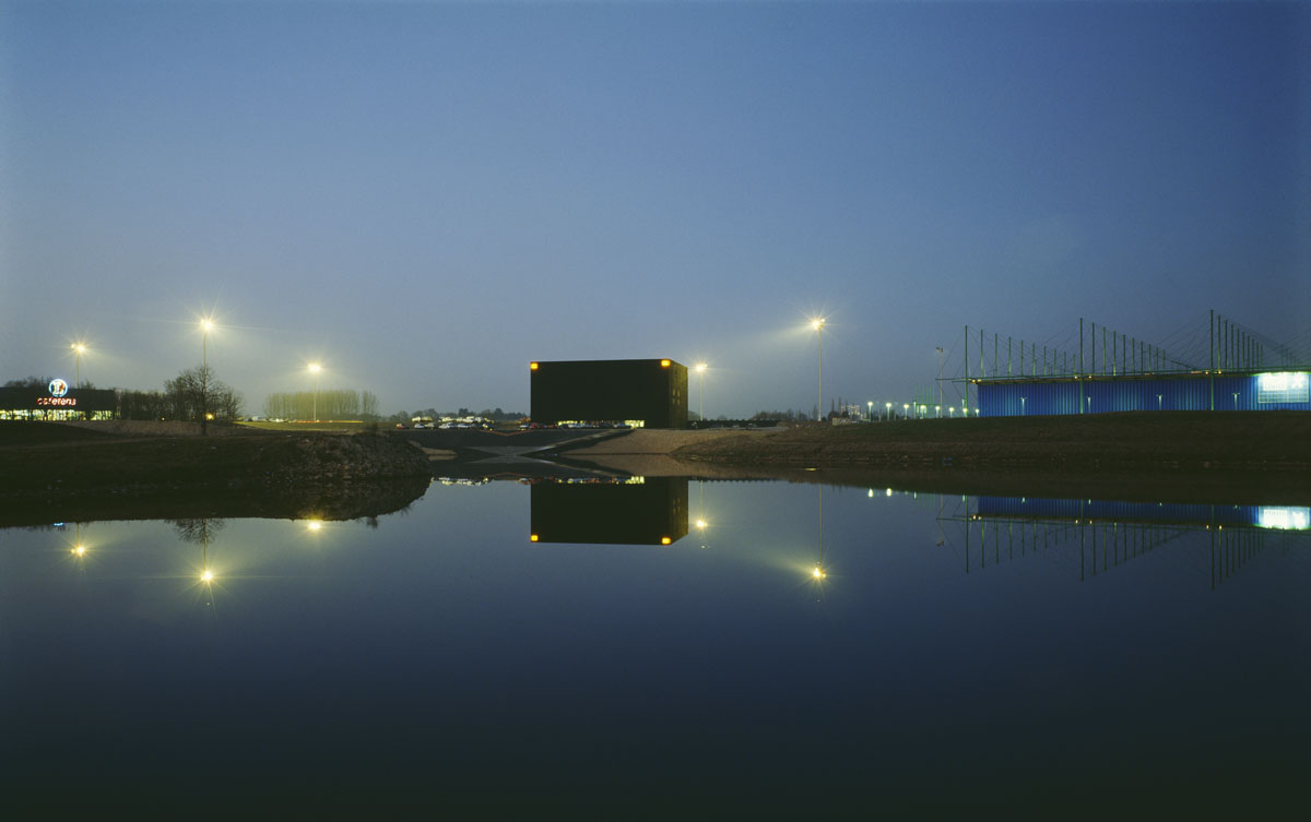 La photographie montre un bâtiment cubique à la tombée du jour.